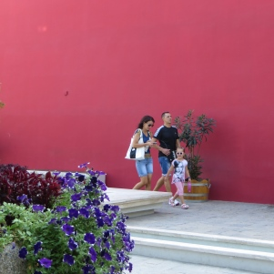 Family in front of signature magenta wall.